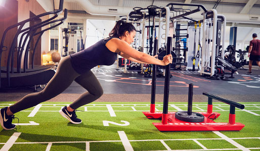 Image of a lady pushing a weighted sled in the gym