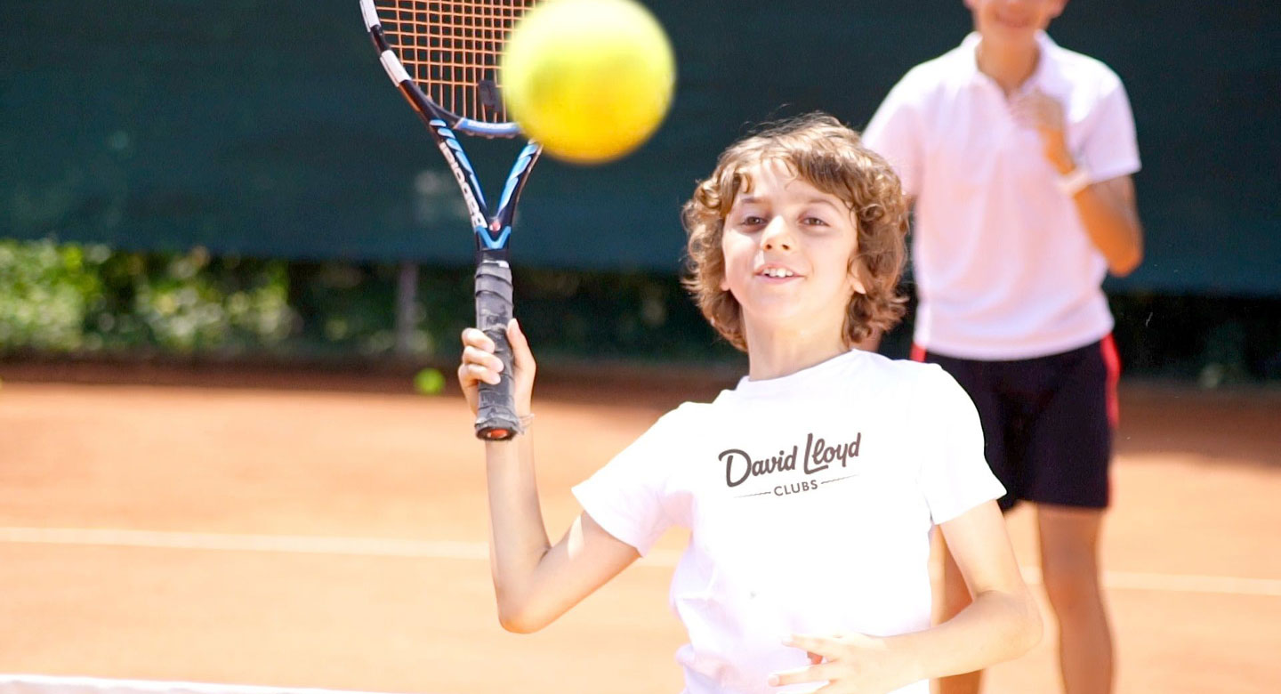 Boy practicing hitting the tennis ball on tennis court