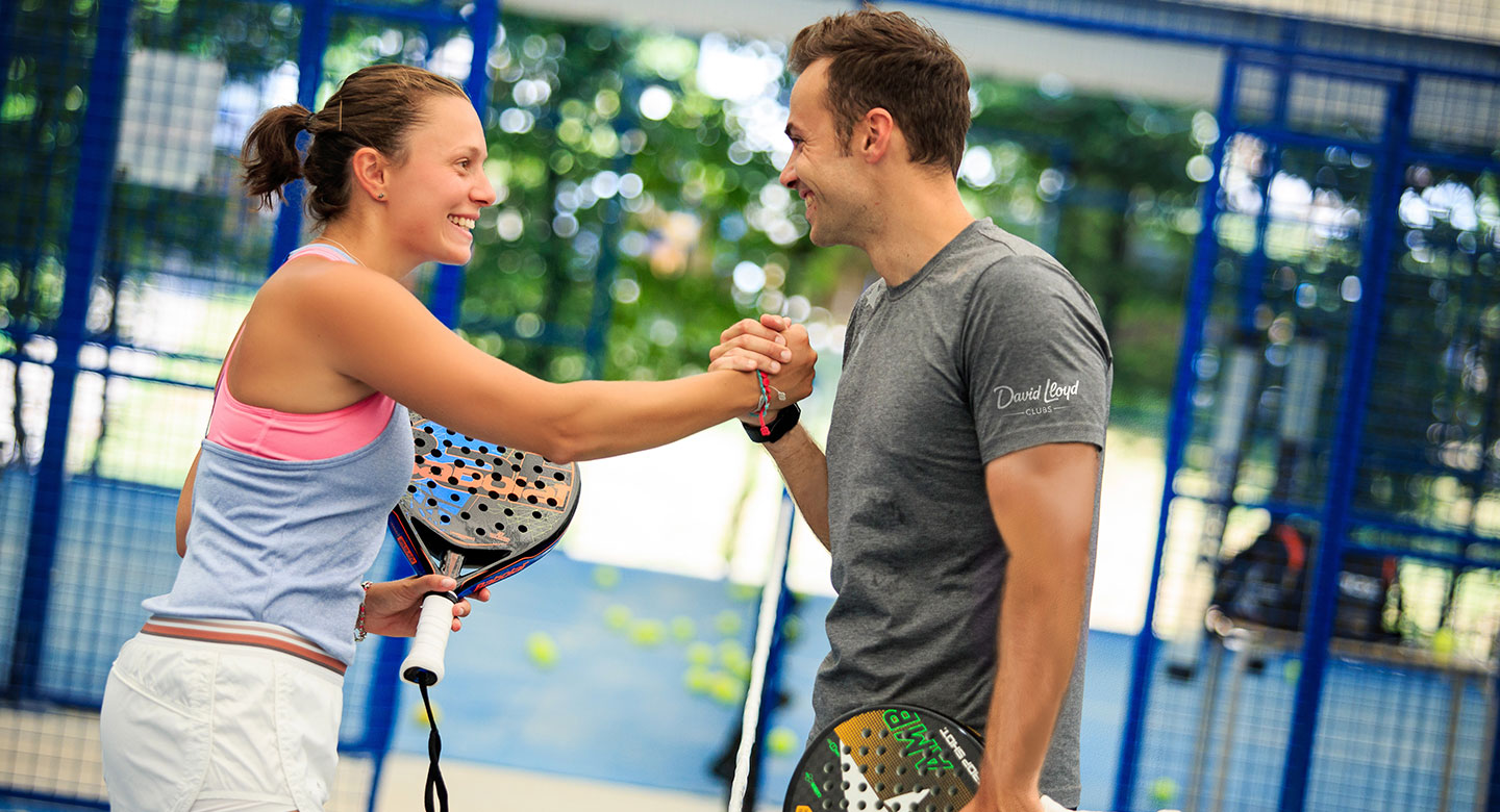 Man and woman shaking hands after padel match
