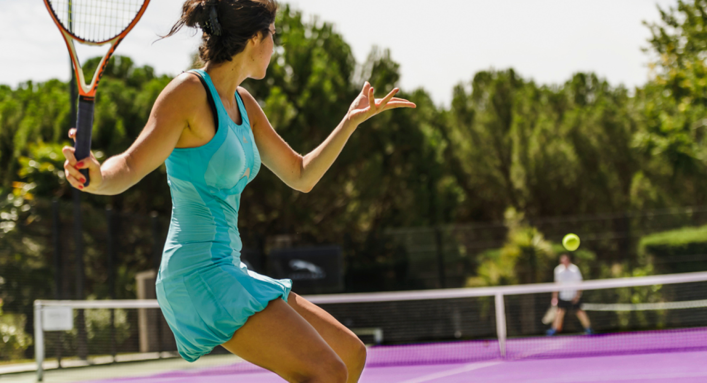 Female tennis player playing tennis outside