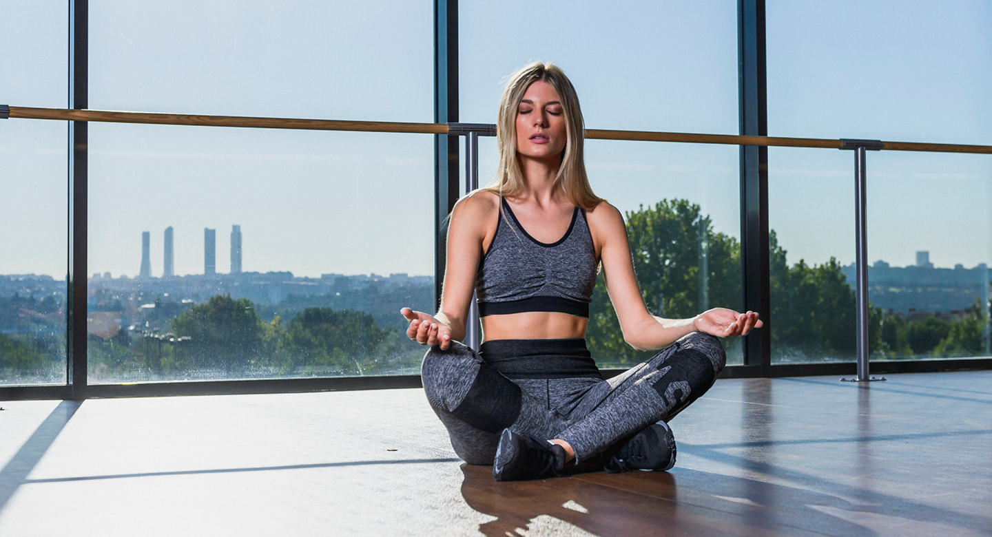 Female performing yoga – behind her is a window with the skyline in the distance