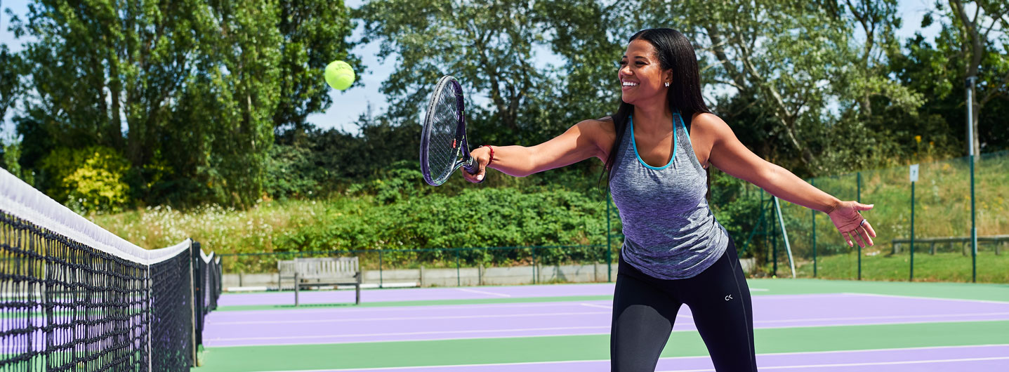Image of lady hitting backhand volley on tennis court at David Lloyd Clubs